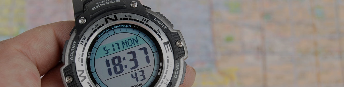 Person holding a digital compass watch over a map blurred out