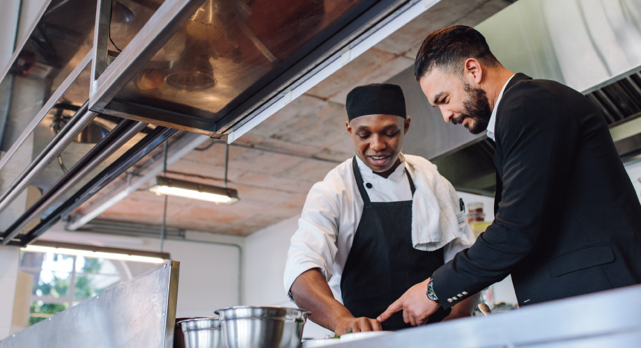 Two men in an industrial kitchen looking at something on a table in front of them.