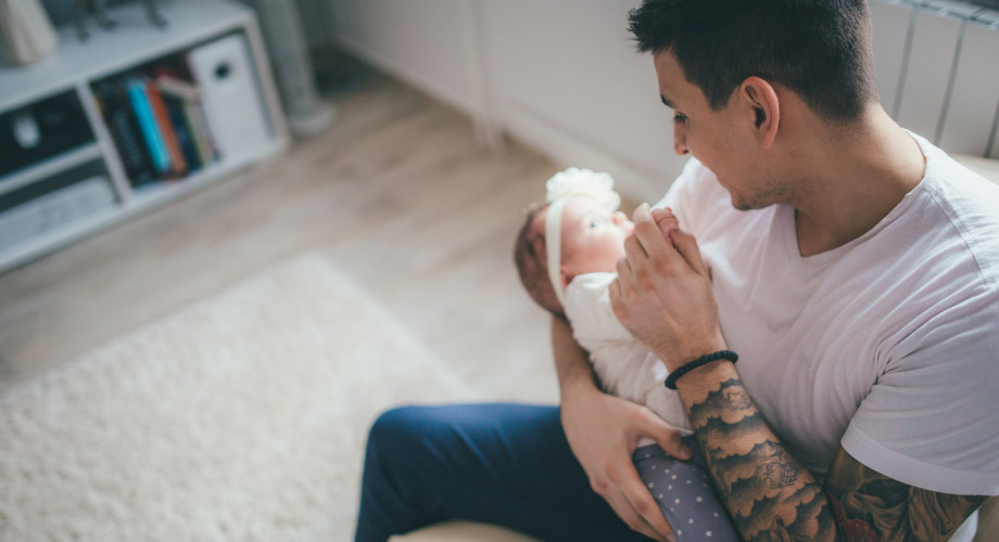 Overhead shot of a dad holding his newborn baby in a living room.