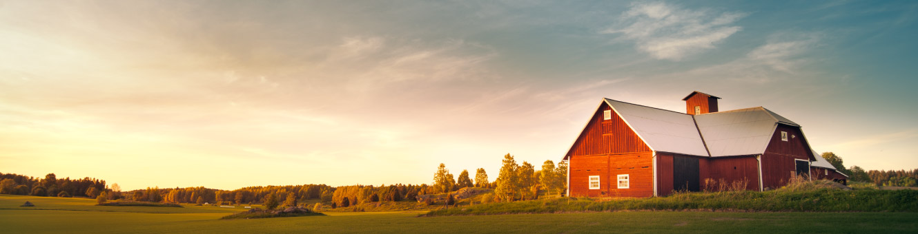 A large red barn with a farm landscape behind it.