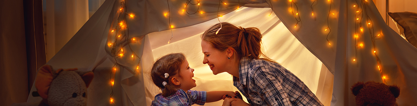 Mother and daughter playing in a tent at home