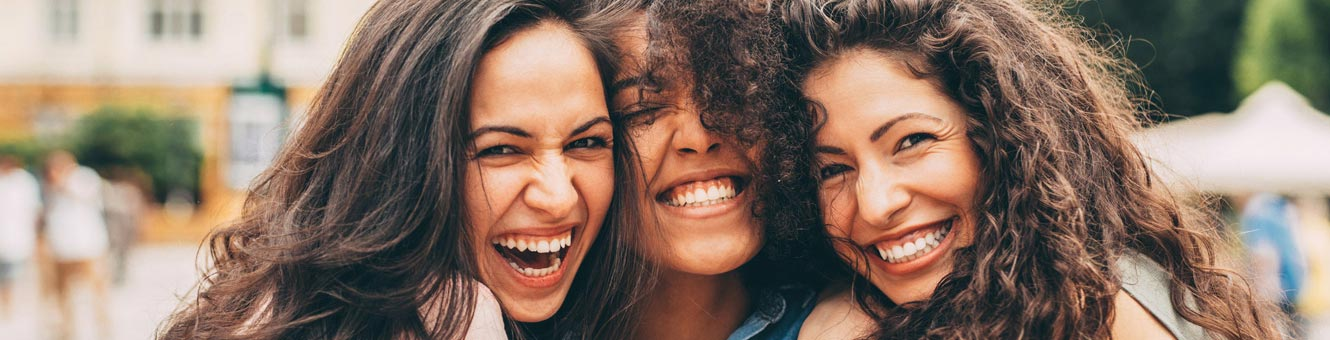 Three young women smiling and laughing together