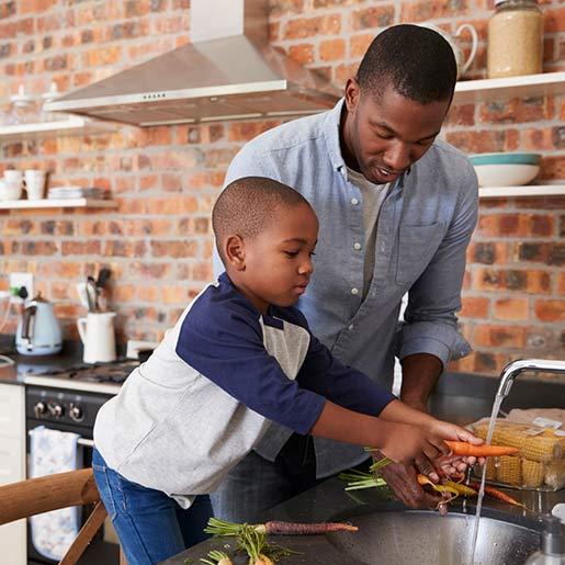 father and his young son washing vegetables in kitchen sink before cooking