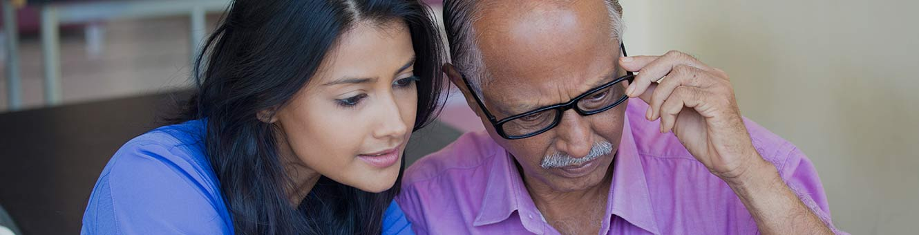 young woman looking at something with her elderly father